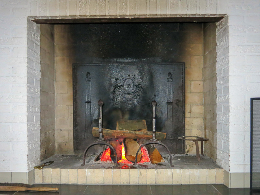 Modern fireplace decorated with antique fireplace accessories