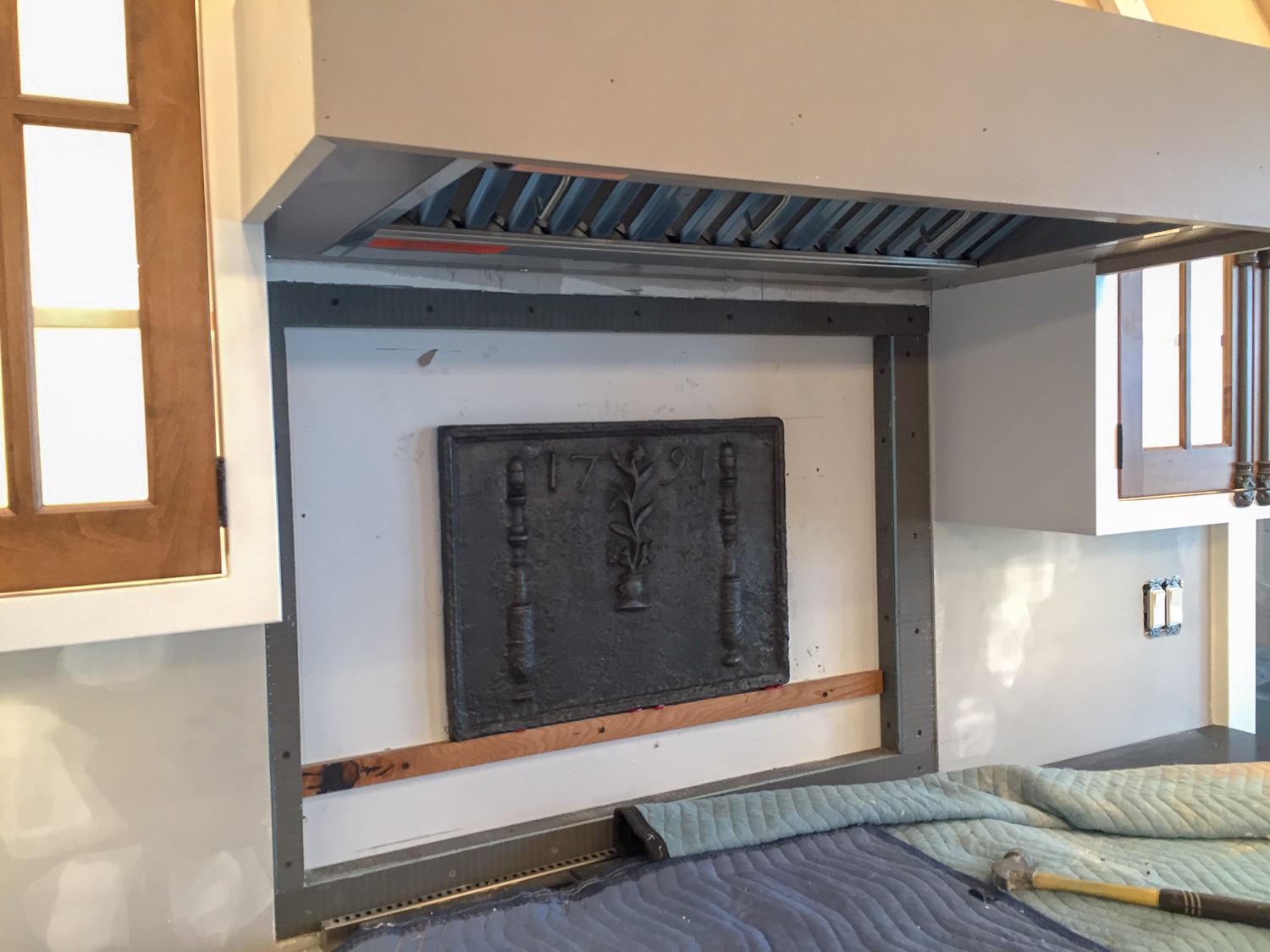 Fireback with construction adhesive for backsplash in a kitchen