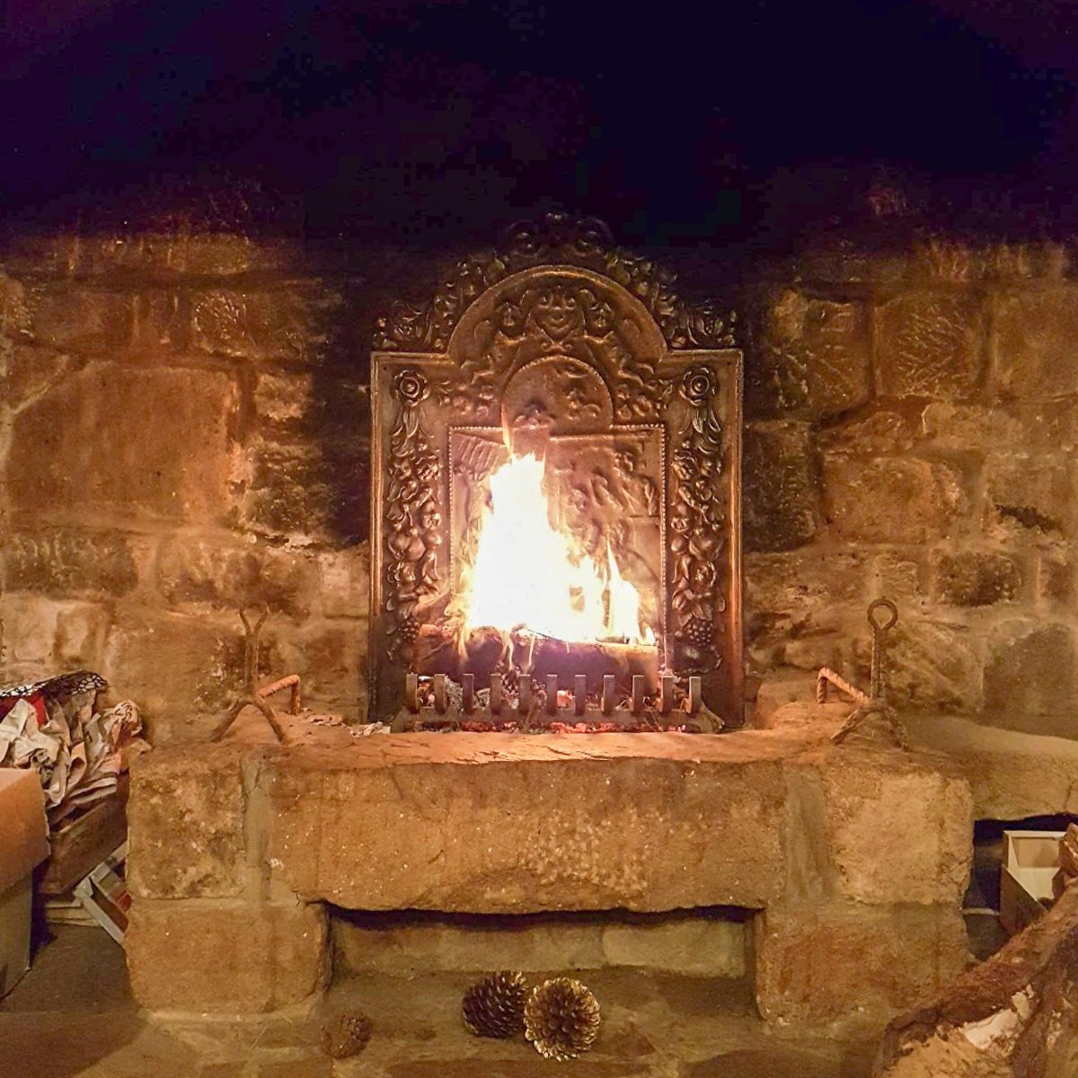 Ugly fireplace beautified with antique fireplace accessories