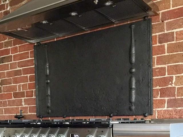 Fireback wall-mounted as backsplash with mounting brackets